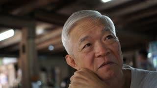 Asian senior man thinking while waiting in restaurant
