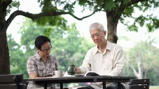Asian senior retire couple drink coffee and read book in park