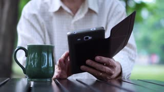 Asian senior use phone while drink coffee in park, morning business lifestyle 4k