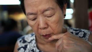 Asian senior woman thinking while looking at menu