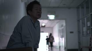 Asian senior woman waiting at hospital corridor worry and sad
