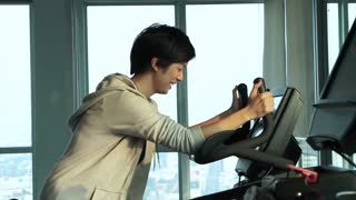 Asian short hair athlete girl cycling gym bicycle at fitness to exercise
