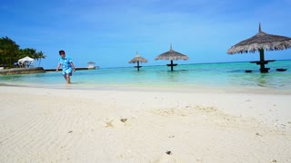 Asian tourist with Hawaiian shirt walking and running around Maldives vacation resort
