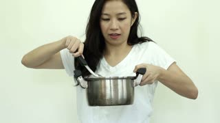 Asian woman cooking with kitchen pot white background slow motion