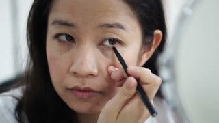 Asian woman doing make up, drawing eyeliner in front of mirror slow motion. Beauty and cosmetic concept