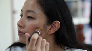 Asian woman doing pink brush on cheek. Model, cosmetic and beauty concept slow motion