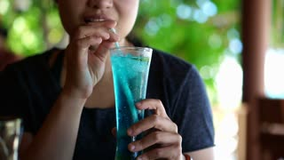 Asian woman drinking blue ocean cocktail at luxury hotel resort beach restaurant