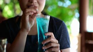 Asian woman drinking blue ocean cocktail at luxury hotel resort beach restaurant