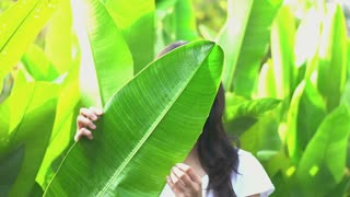 Asian woman hiding her expression behind tropical leaf. Upset and angry, emotion management concept