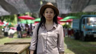 Asian woman smiling wearing hat standing local farmer market. Buy organic and home grown product from community