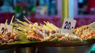 Assorted meat ball, hot dog and sausage on skewers selling at night food market of Thailand