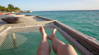 Bare feet on over ocean bed net at beautiful tropical paradise Maldives sea