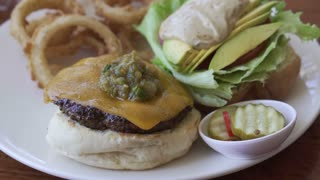 Beef cajun cheese burger with avocado and onion rings side