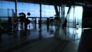 Blur crowd of people silhouette walking in airport with glass structure and sunrise background. Abstract business and traveler