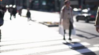 Blur shot of anonymous Japanese people walking in beautiful sun crossing and along pedestrian street in Tokyo