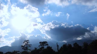 Bright blue sunny cloudy summer sky with mountain silhouette 4k