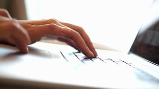 Close up of a young freelancer woman hands typing on a laptop keyboard at home
