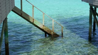 Crystal clear ocean at Maldives. Pole and stair of private villa resort architecture building on beautiful paradise island