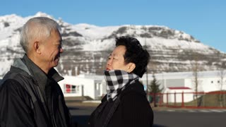 Cute Asian senior couple happy honeymoon anniversary trip in Europe snow alp. Kissing on cheek