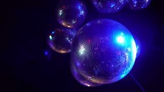 Disco ball spinning colorful light ray in nightclub retro bar