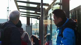 Editorial: Amsterdam, Netherlands - April 2017: Asian tourist family waiting for tram transportation for city travel in the morning. Slow motion 120 fps