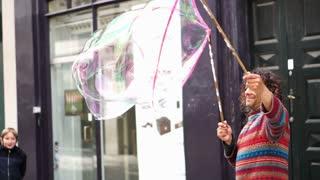 Editorial: Copenhagen, Denmark: April 2017 - Street artist creating big soap bubble in downtown area for entertaining pedestrian