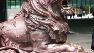 Editorial: Hong Kong - April 2016:Wet lion statue at the entrance of HSBC Bank head quarter Tower in Central District, Hong Kong in the rainy day