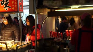 Editorial: Taipei, Taiwan: February 2016: People buying food in front of vendor stalls around Shilin night market