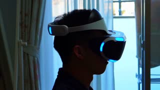 Editorial: Tokyo, Japan- December 2016: Asian man playing VR game headset at home. New technology for game and virtual reality