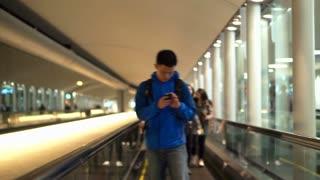 Editorial: Tokyo, Japan - December 2017: Asian backpacker man checking using smart phone at airport