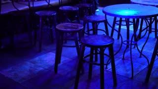 Empty night club pub table under purple disco light