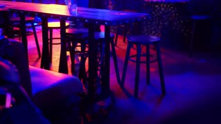 Empty table in night pub with colorful light shining