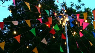 Festival event decoration. Colorful flags and light hanging over pole in evening sky