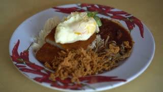 Hand mixing and eating nasi lemak Singapore, Malaysian famous food