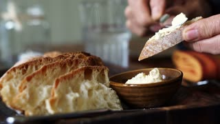 Hand spreading butter on fresh bake bread rustic food style