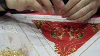 Hand stitching gold thread on clothes. Handmade traditional art style video