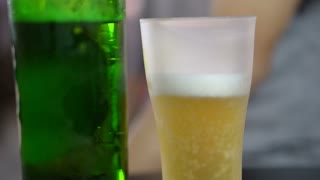 Hand taking frosted beer glass to drink