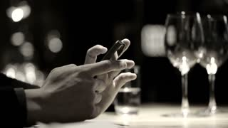Hand using smartphone in luxury restaurant with wine glasses black and white