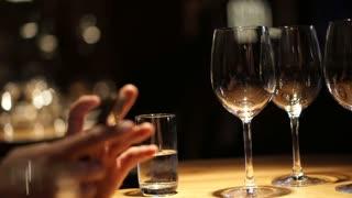 Hand using smartphone in luxury restaurant with wine glasses