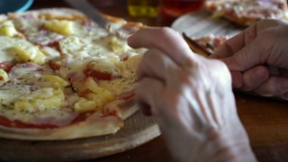 Hands taking melted cheese homemade pizza at party