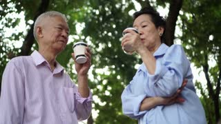 Happy Asian elderly couple morning walk in green city while drinking coffee and talking