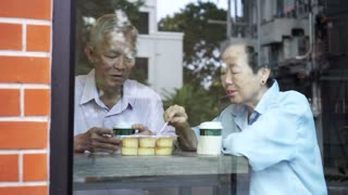 Happy Asian elderly senior couple drinking morning coffee through cafe glass front