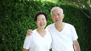 Happy Asian senior couple green bush nature background 4k