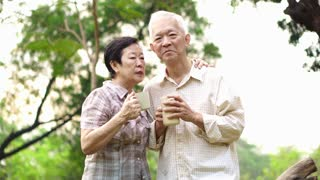 Happy Old Asian senior couple dating at park in the morning. Coffee conversation