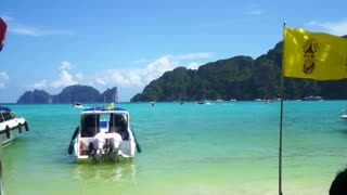 Krabi, Thailand beautiful blue paradise ocean view with speed boat on shore. Together with Thai national and King Rama IX flags
