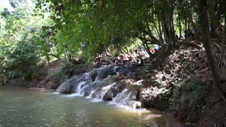 Krabi, Thailand - May 2016: Group of tourists playing tropical waterfall in Thailand