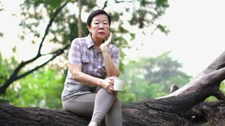 Lonely Asian senior woman sitting looking sad drinking coffee alone in park thinking about life