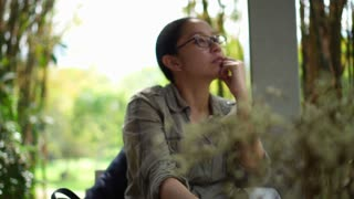 Mixed race Asian woman sit relax and thinking in cafe garden