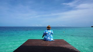 Person sitting at wood deck relax at peaceful and calm sea and nice sky