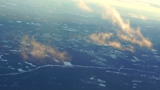 Plane soaring through cloud, aerial view of city and ocean slow motion video
